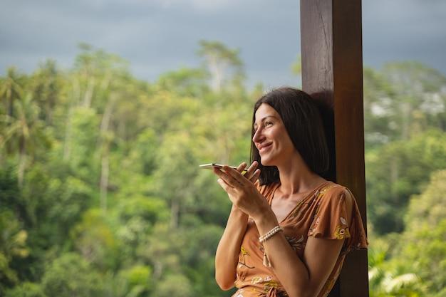 Fröhliche brünette weibliche person, die ein lächeln auf ihrem gesicht hält, während sie ein angenehmes telefongespräch führt