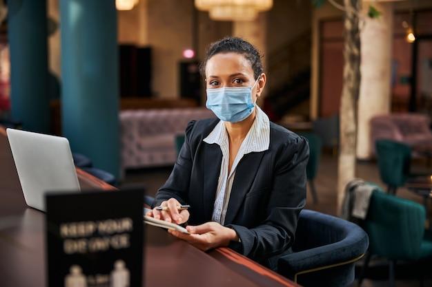 Fröhliche brünette weibliche person, die eine sterile maske trägt, während sie an öffentlichen orten arbeitet working