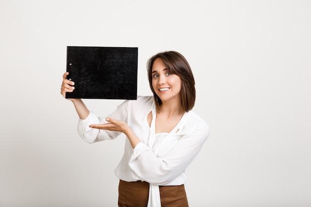 Fröhliche bürodame, die banner auf schwarzer zwischenablage zeigt