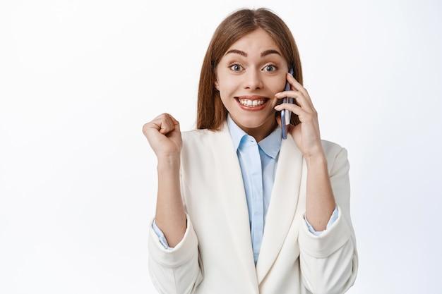 Fröhliche bürofrau, elegante dame im weißen anzug beantwortet telefonanrufe und springt vom glück, erhält großartige neuigkeiten, gewinnt und feiert, steht über weißer wand