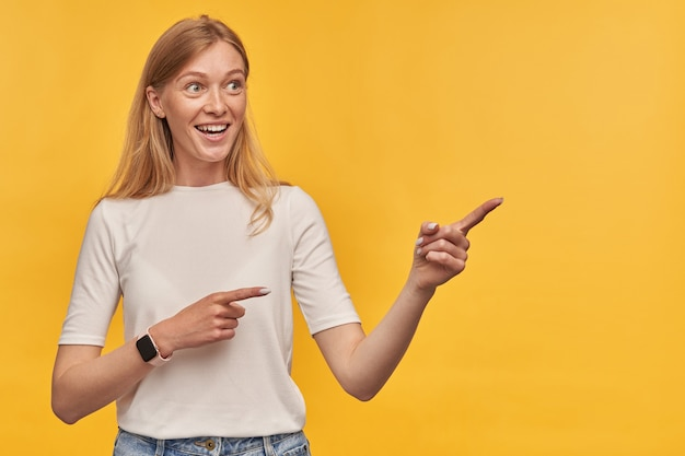 Fröhliche, charmante blonde junge frau im weißen t-shirt mit sommersprossen und intelligenter uhr, die auf die seite am exemplar über der gelben wand zeigt?