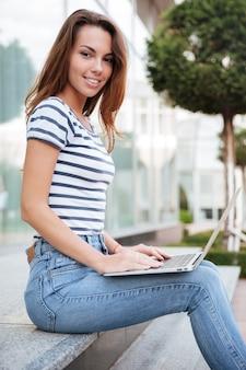 Fröhliche charmante junge frau, die draußen mit laptop lächelt und arbeitet