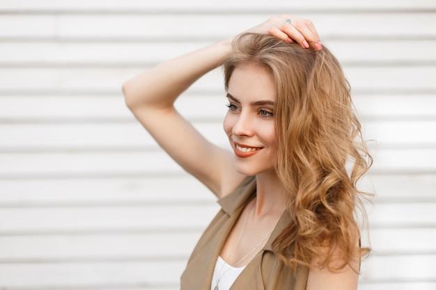 Fröhliche charmante junge frau mit einem wunderbaren lächeln mit lockigem blondem haar in einer stilvollen weste, die nahe einer weißen hölzernen weinlesewand an einem warmen sommertag aufwirft. glückliches positives stilvolles mädchen.