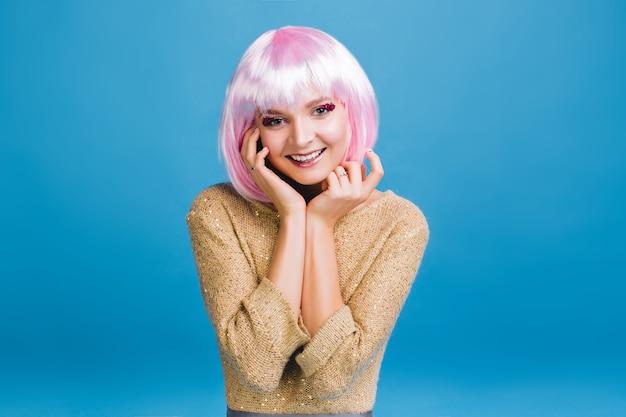 Fröhliche charmante junge frau mit leuchtend rosa lametta make-up lächelnd. glückliche zeit, rosa geschnittenes haar, fantasie, neujahrsparty feiern, geburtstag.