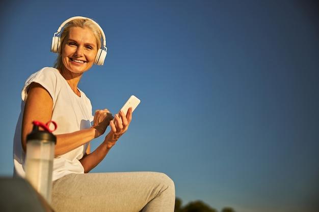 Fröhliche dame, die handy hält und lächelt, während sie musik über drahtlose kopfhörer unter blauem himmel hört. website-banner
