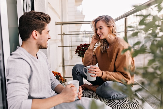 Fröhliche dame, die mit ehemann am balkon spricht. charmante junge frau, die tee an der terrasse trinkt.