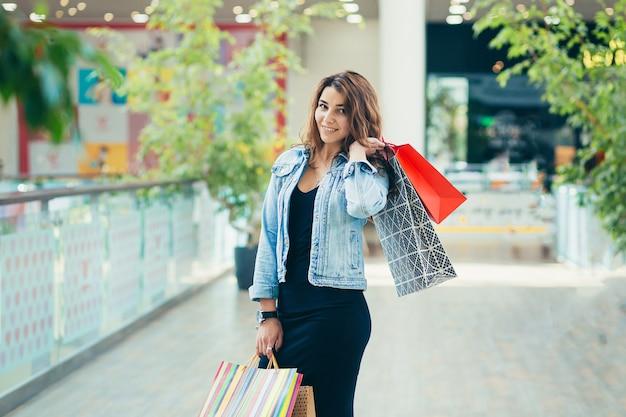 Fröhliche dame im stilvollen schwarzen kleid, das bunte einkaufstaschen beim gehen am laden weiterführt