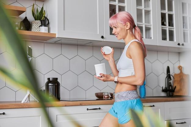 Fröhliche dame im trainingsanzug zeigt ein offenes glas nahrungsergänzungsmittel zur kamera in der küche