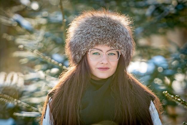 Fröhliche dame in gläsern und winterkleidung, die mit freude draußen im schneewald aufwirft