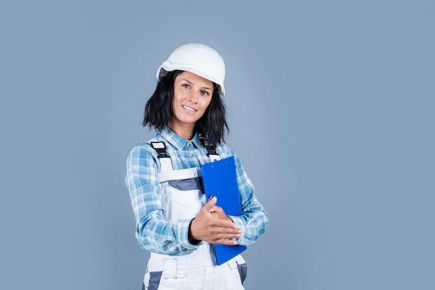 Fröhliche dame mechaniker in uniform auf blauem hintergrund, werkstatt.