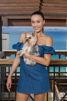 Fröhliche dame mit hund auf überdachter terrasse
