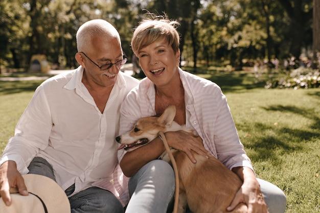 Fröhliche dame mit kurzen blonden haaren im rosa hemd, das lacht, hund umarmt und auf gras mit grauhaarigem mann in brillen im park sitzt.