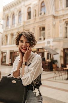 Fröhliche dame mit welligem haar in bluse mit schwarzer spitze, die über straße lacht. trendy dame in jeans mit handtasche, die in der stadt aufwirft.