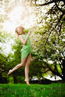 Fröhliche dame springt im grünen garten