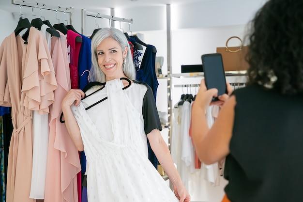 Fröhliche damen genießen das einkaufen im modegeschäft zusammen, halten kleid und machen fotos auf dem handy. konsum- oder einkaufskonzept