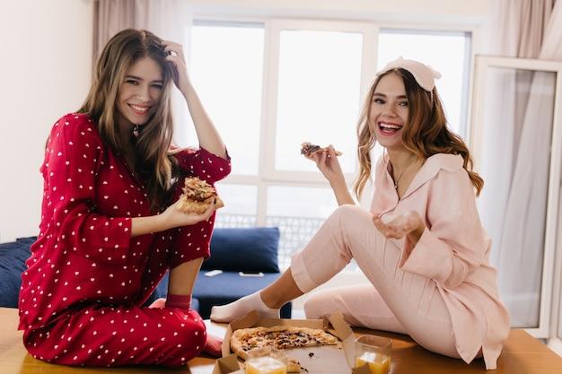 Fröhliche damen tragen pyjamas und socken, die zusammen pizza essen. innenfoto von zwei lachenden mädchen, die spaß während des frühstücks haben.