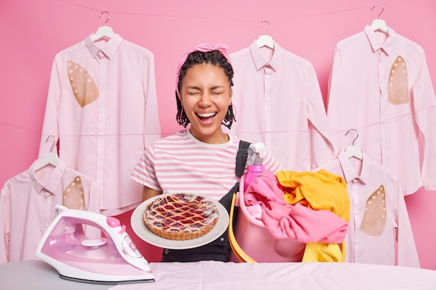 Fröhliche dunkelhäutige afroamerikanerin, die an der hausarbeit beteiligt ist, hat viele verantwortungen hält einen eimer mit wäsche köstlich gebackener kuchen posiert in der nähe des bügelbretts drückt positive emotionen