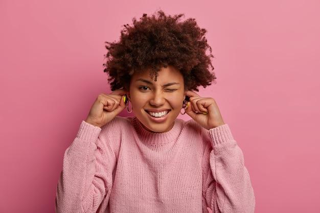 Fröhliche dunkelhäutige gestörte frau steckt die ohren zu, ignoriert laute musik, ist auf party, will keinen lärm hören, hat lockige frisur, trägt einen pullover, posiert vor rosa pastellfarbenem hintergrund. dezibel
