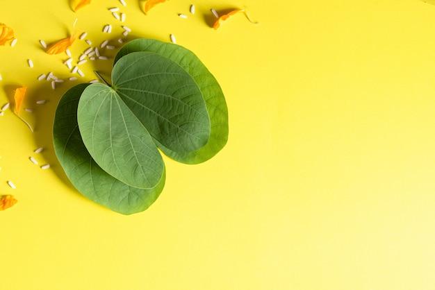 Fröhliche dussehra. gelbe blumen, grünes blatt und reis auf gelbem hintergrund.