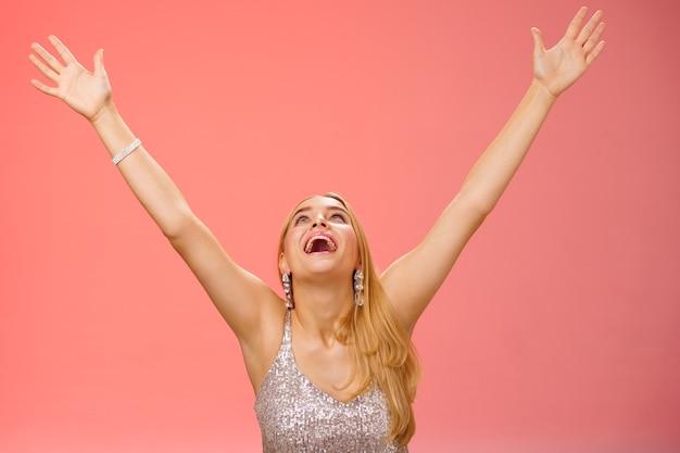 Fröhliche emotionale lächelnde überwältigte junge blonde frau in silbernem kleid hebt die hände himmel gott sei dank freudig unterzeichneter vertrag bekam job und freute sich auf rotem hintergrund, der den sieg feierte, gute nachrichten, triumphierend.