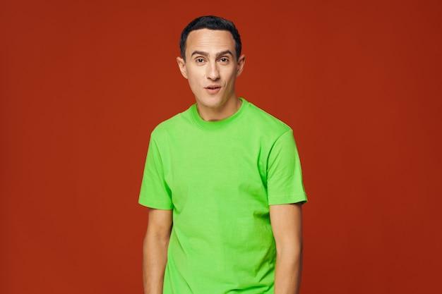 Fröhliche emotionen des fröhlichen emotionalen mannes grünes t-shirt lebensstil