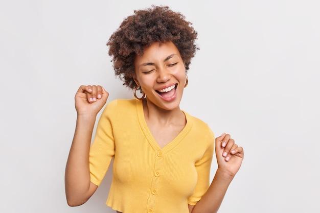 Fröhliche entspannte frau fängt sorglosen moment genießt freiheit singt lied hält arme hoch, schließt augen tanzt zu lieblingsmusik trägt lässiges gelbes t-shirt isoliert auf weißer wand