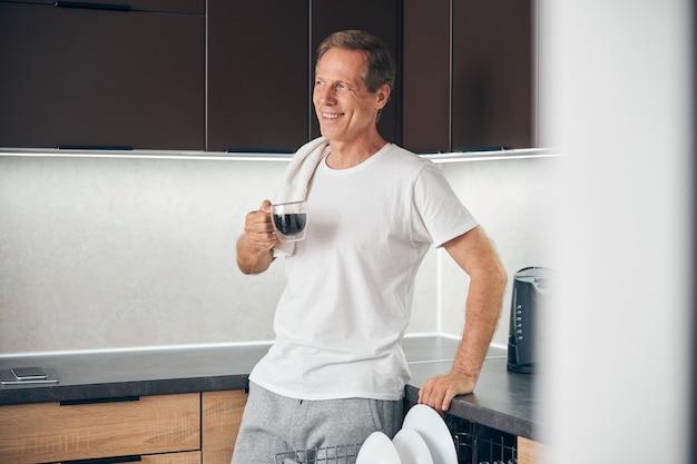 Fröhliche, entspannte männliche person, die ein lächeln auf dem gesicht hält, während sie aromakaffee in der küche trinkt