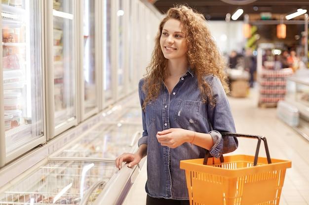 Fröhliche entzückende lockige frau in jeansjacke, hält einkaufskorb, spaziert im supermarkt, ist gut gelaunt. hübsche frau kommt zum lebensmittelgeschäft, um die notwendigen produkte zu kaufen