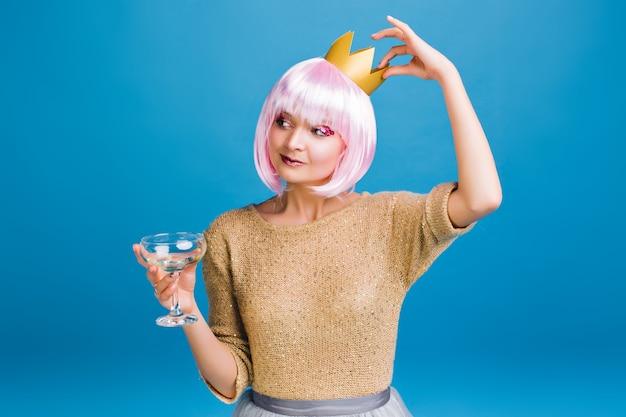 Fröhliche erstaunliche junge frau mit rosa haarschnitt, die spaß hat. goldene krone auf kopf, leuchtendes make-up mit rosa lametta, champagner, neujahrsparty feiern, lächelnd.