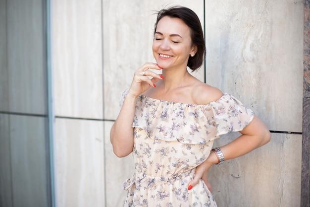 Fröhliche erwachsene frau im kleid, die mit geschlossenen augen lächelt. festtag am 8. märz konzept für weiblichkeit und schönheit