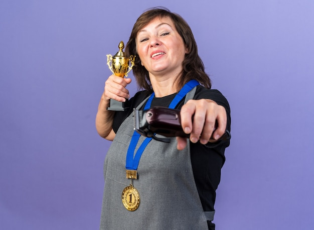 Fröhliche erwachsene friseurin in uniform mit goldener medaille um den hals, die haarschneidemaschine und siegerpokal einzeln auf lila wand mit kopierraum hält