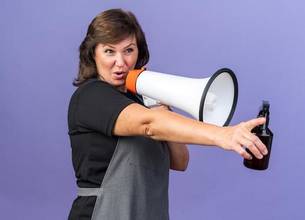 Fröhliche erwachsene friseurin in uniform mit lautsprecher und sprühflasche isoliert auf lila wand mit kopierraum