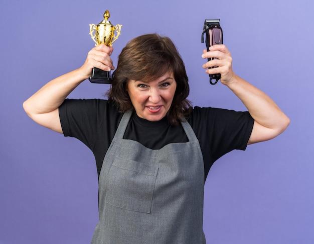 Fröhliche erwachsene weibliche friseurin in uniform mit haarschneidemaschine und siegerpokal isoliert auf lila wand mit kopierraum