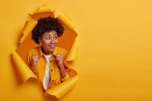 Fröhliche ethnische dame ballt die fäuste und schaut zur seite, fühlt sich sehr glücklich und optimistisch, feiert den sieg oder gewinnt die lotterie, aufgeregt über das positive ergebnis, steht in einem zerrissenen papierloch.