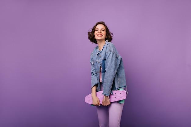 Fröhliche europäische frau in der lila hose, die mit skateboard aufwirft. innenaufnahme des ansprechenden lächelnden mädchens mit dunklem welligem haar.