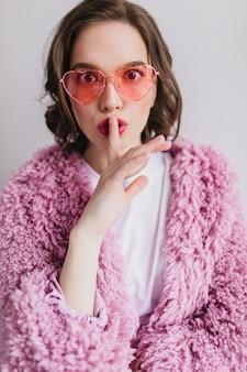 Fröhliche europäische junge frau im trendigen flauschigen mantel, der ihre lippen mit finger berührt. erstaunliches anmutiges mädchen in der sonnenbrille lokalisiert auf weißer wand.