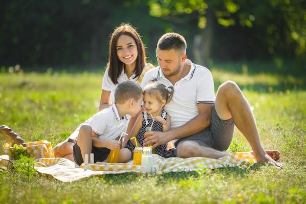Fröhliche familie beim picknick. eltern essen mit ihren kindern im freien zu abend.