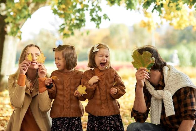 Fröhliche familie, die spaß mit herbstlichen blättern im wald hat
