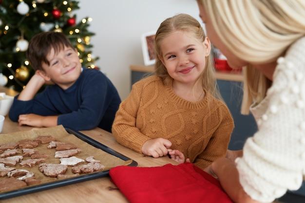 Fröhliche familie, die über gerade gemachte weihnachtsplätzchen spricht