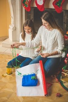 Fröhliche familie, die weihnachtsgeschenke am kamin einpackt