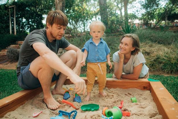 Fröhliche familie, die zusammen im sandkasten spielt