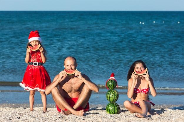Fröhliche familie feiert sommerweihnachtsvater und zwei töchter, die wassermelone am strand essen