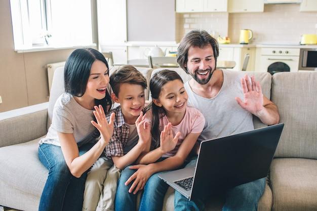 Fröhliche familie hat laptop und winkt mit den händen