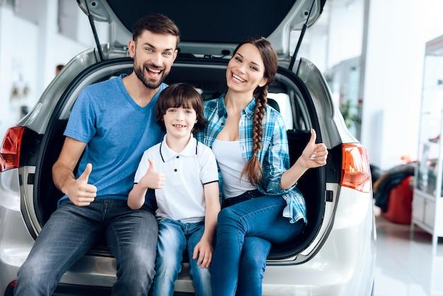 Fröhliche familie lächelt beim sitzen im kofferraum.