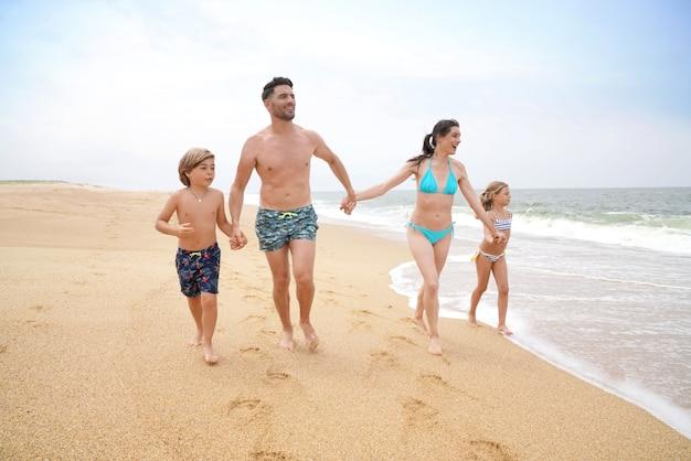 Fröhliche familie läuft am sandstrand