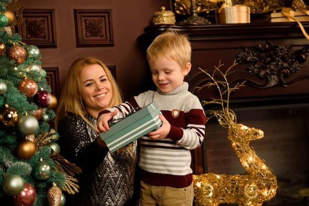 Fröhliche familie mit weihnachtsgeschenken am baum.