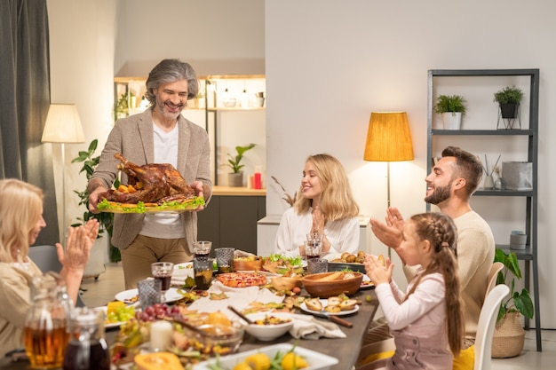 Fröhliche familie sitzt am festlichen tisch, serviert mit hausgemachtem essen und klatschen in die hände, während sie den reifen mann begrüßt, der gebratenen truthahn trägt