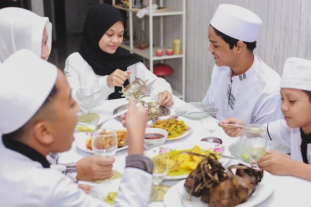 Fröhliche familie versammelt sich und isst zusammen im speisesaal während der eid mubarak-feier