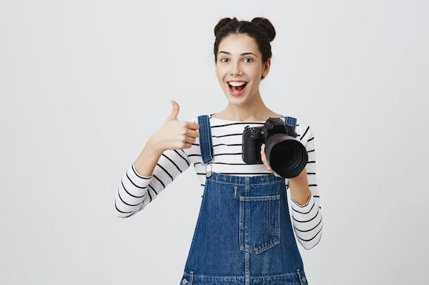 Fröhliche fotografin zeigt daumen hoch, lobt die gute arbeit des models und macht komplimente