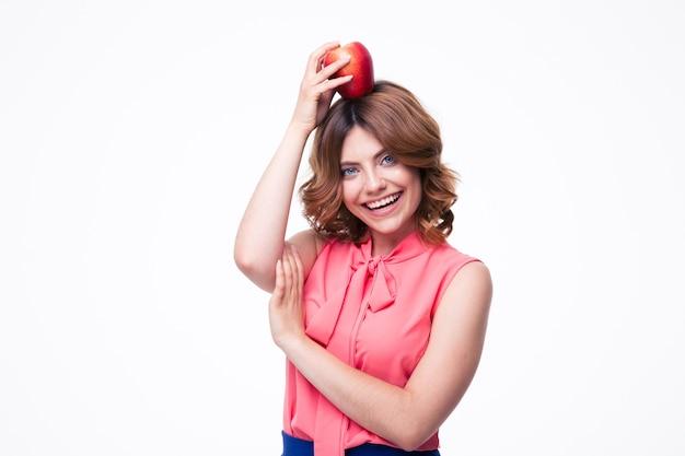 Fröhliche frau, die äpfel auf kopf hält
